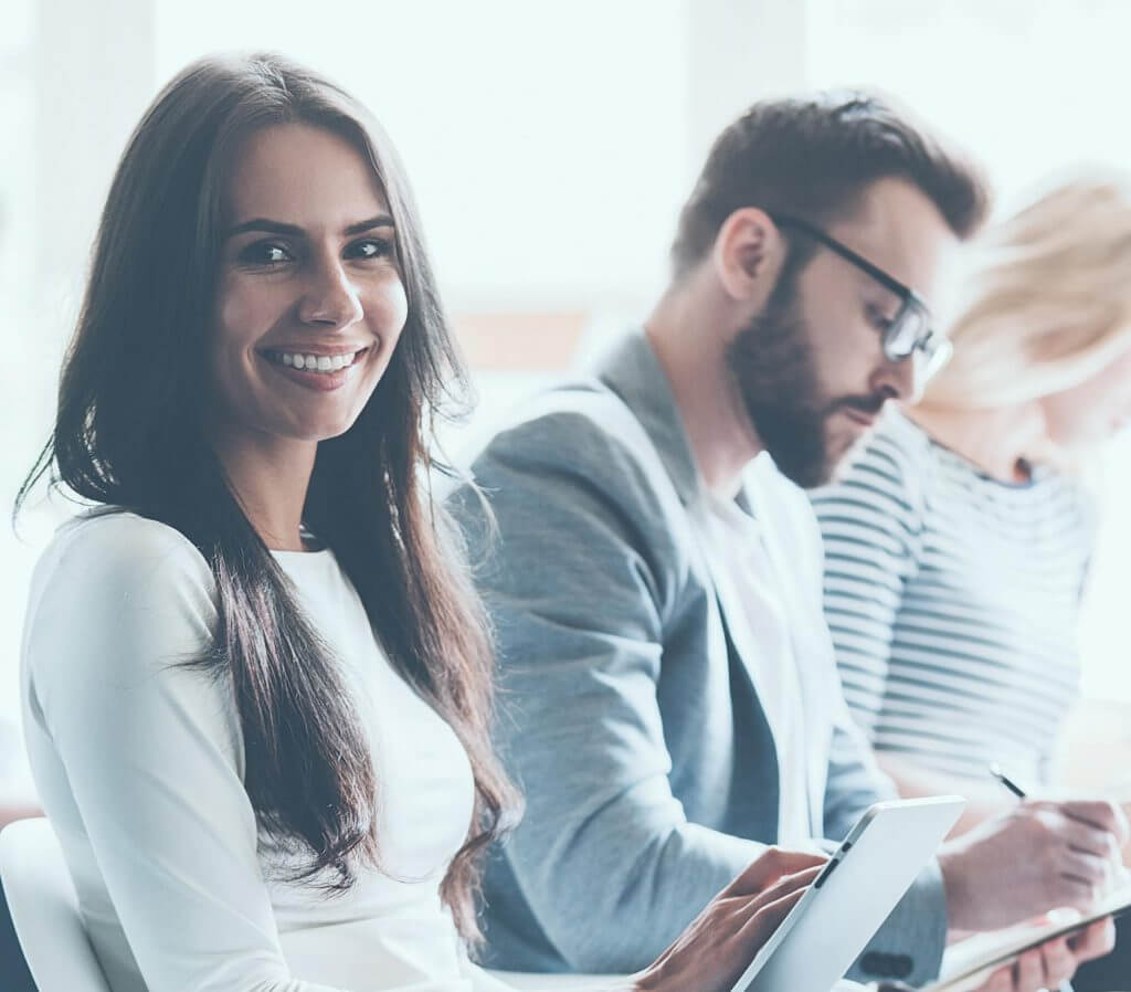 Woman smiling while taking notes in a meeting.